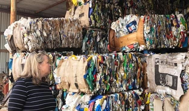 woman in front of recycling bundles
