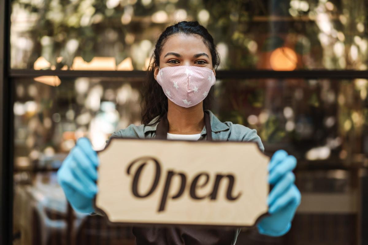 female business owner with Open sign