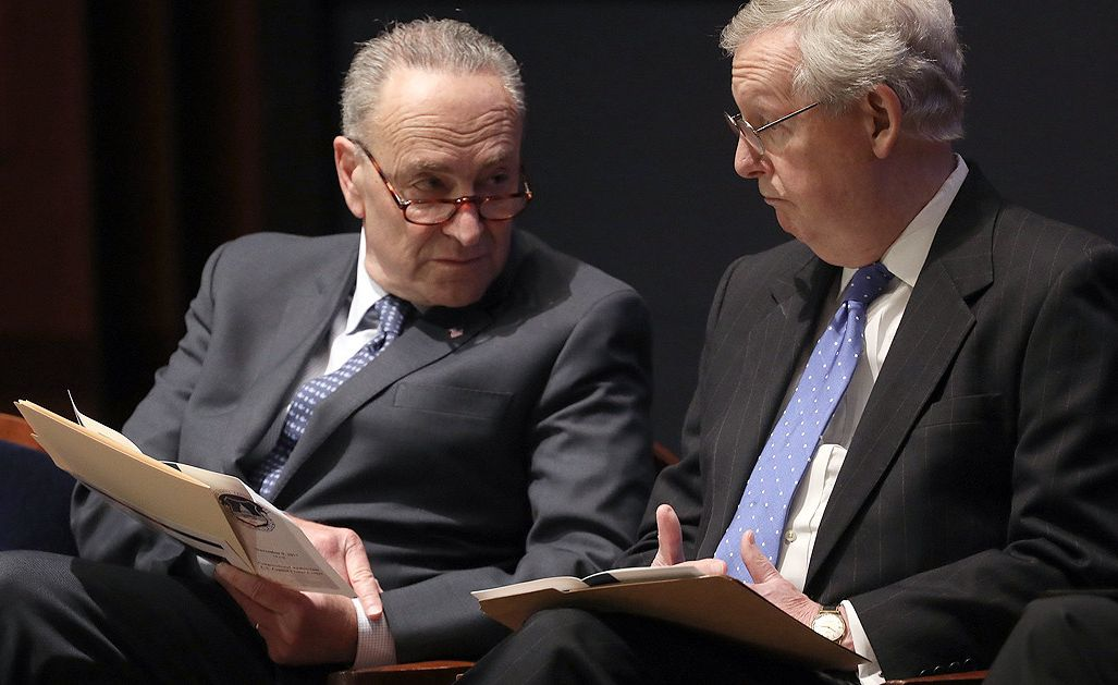 senator chuck schumer and another man in a suit talking with papers in their hands
