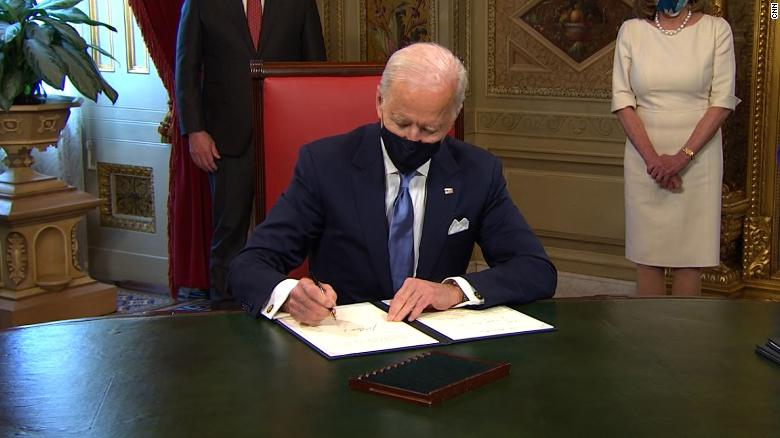 President Biden signing papers in a mask