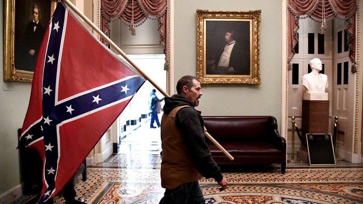 Rioter in Capitol with Confederate flag