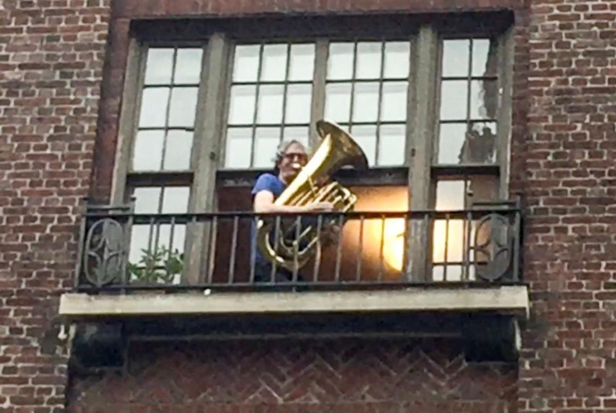 man playing tuba on apartment balcony