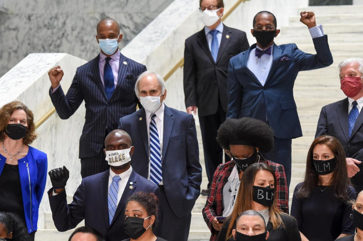 people in suits wearing masks and standing in support of black lives