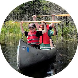 A group of campers celebrating in their canoe
