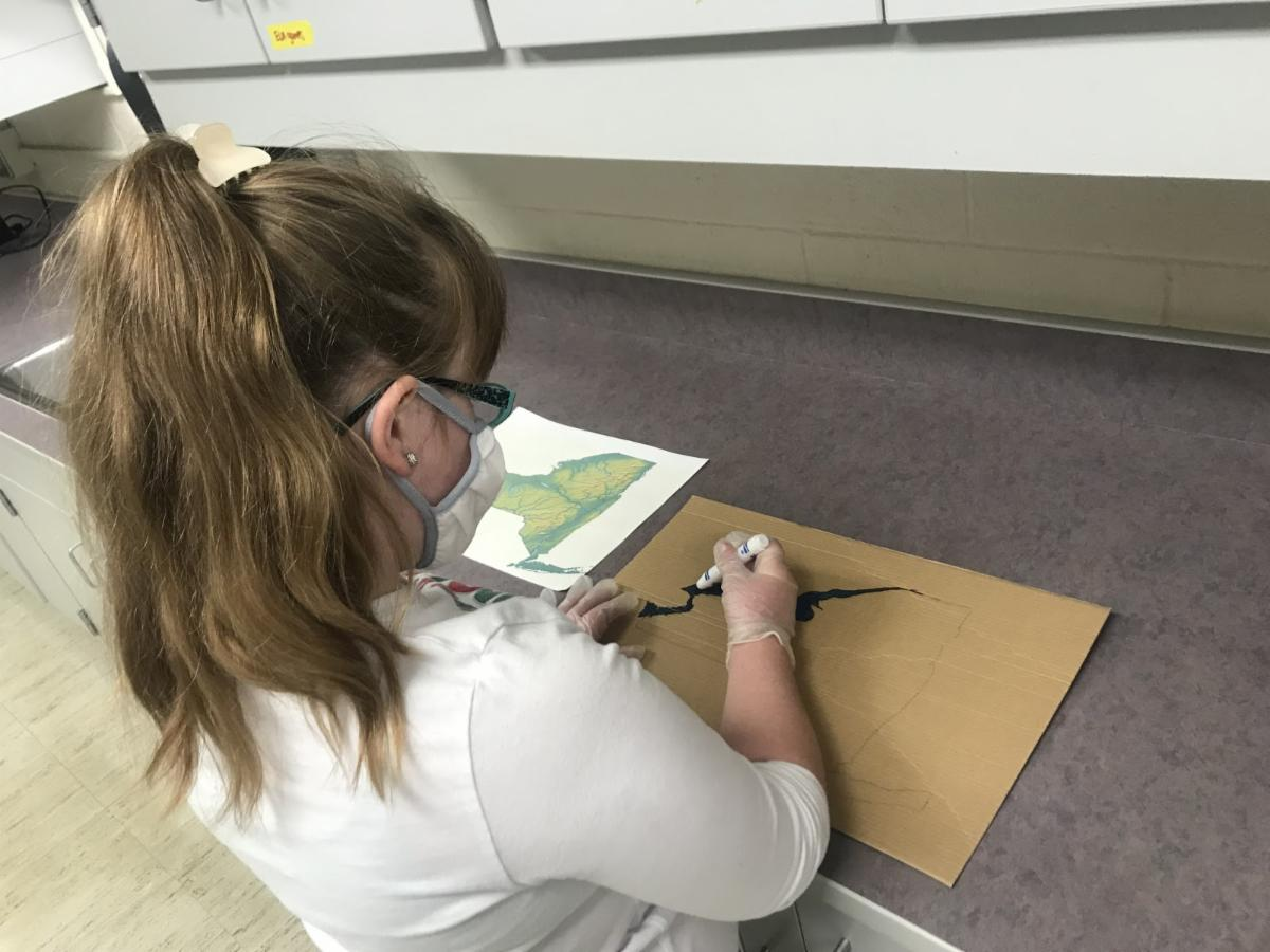 student drawing a map of the five nations