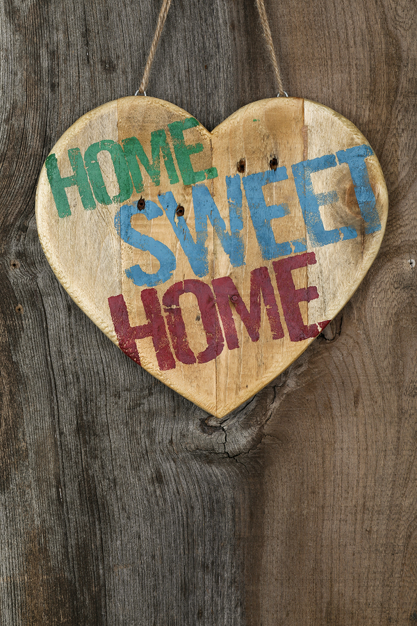 Home Sweet Home  message wooden heart sign from recycled old palette on rough grey wooden background copy space