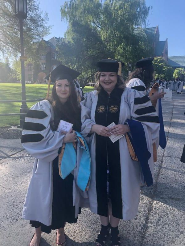 Two women standing side by side in UI graduation robes.