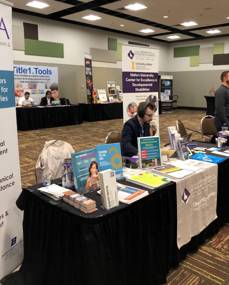 CDHD staff sits at the vendor booth display table