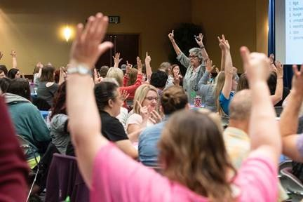 conference attendees raise their arms during a session activity.