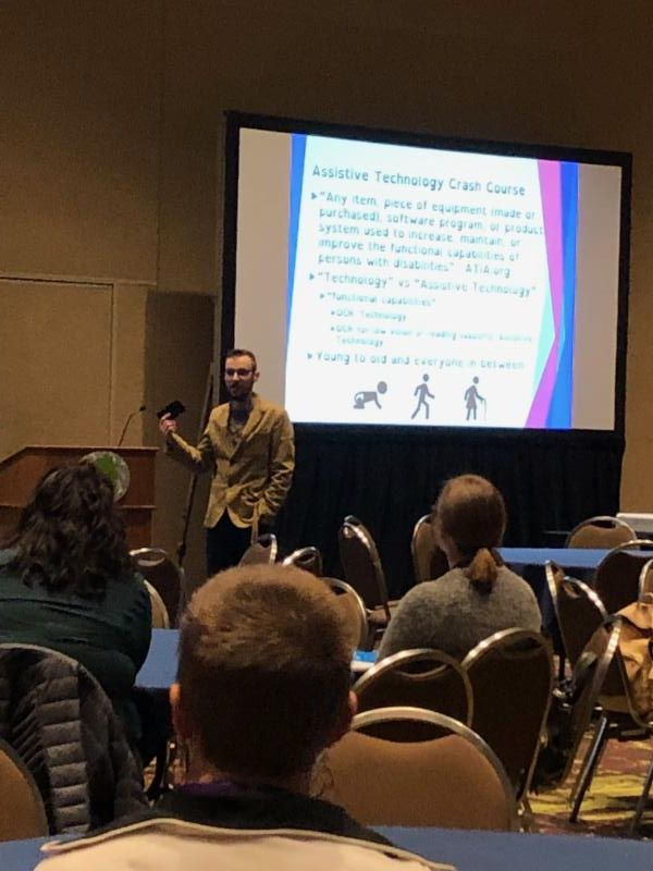 Nick Stallings presents in front of an audience of conference attendees.