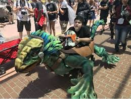 Photo of a child in a wheelchair that has been modified to look like a dragon.