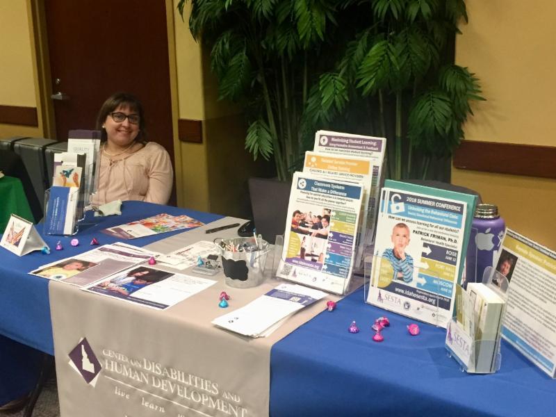 Carly Saxe sits at CDHD display table at PBIS conference.