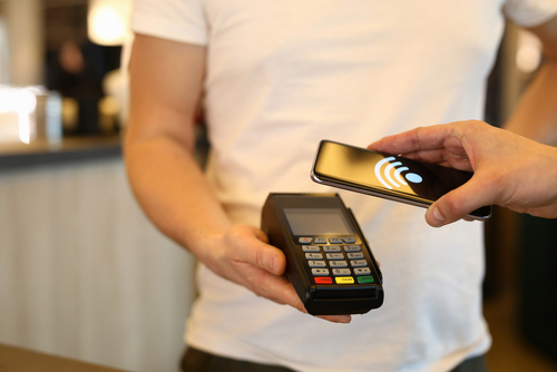 Close-up of customer person making payment via terminal and mobile phone in cafe. Pay by smartphone. Contactless nfc and modern device technology concept
