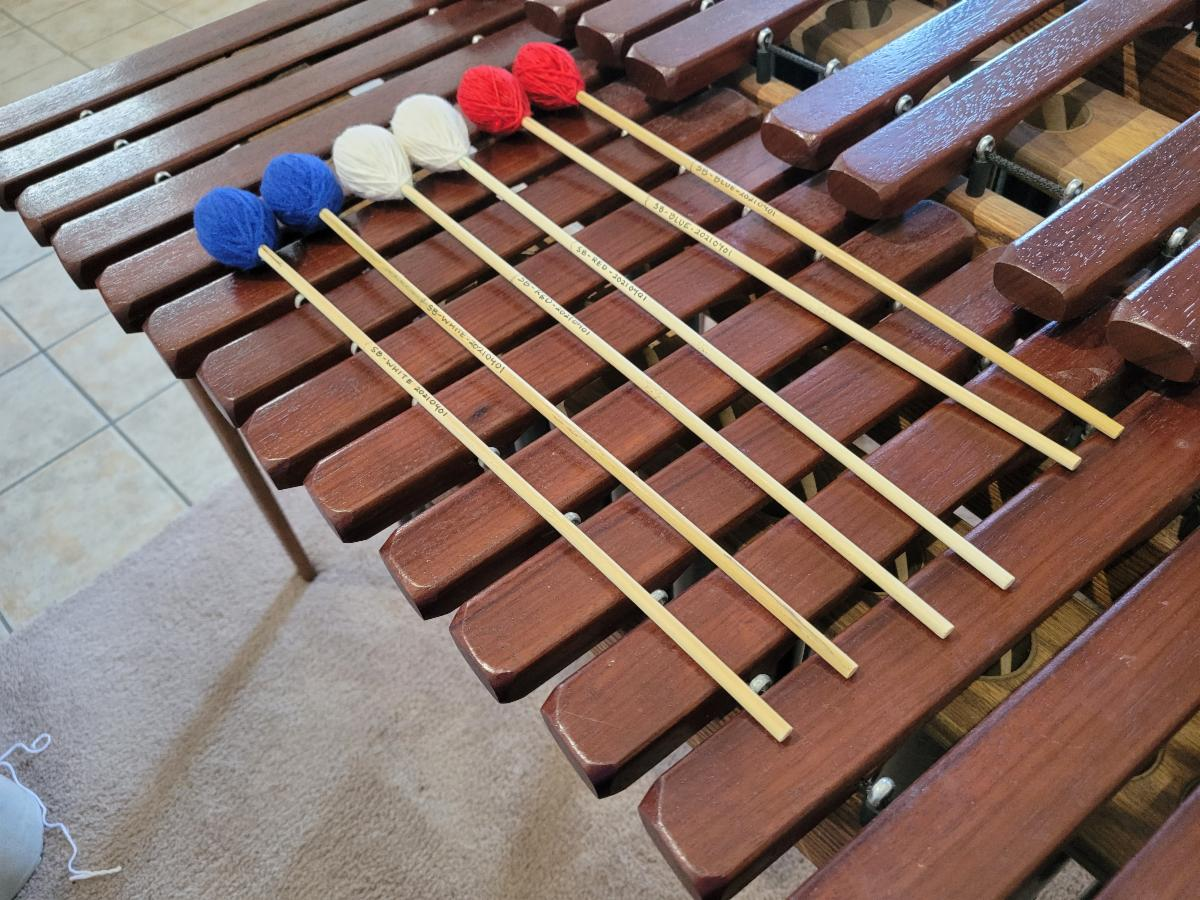 Six custom made musical mallets placed on a xylophone