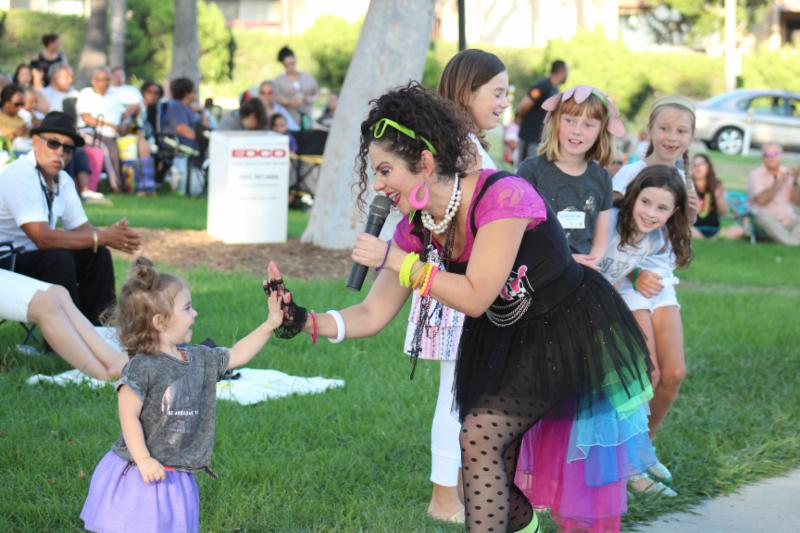 Photo from Concerts in the Park with lead singer high-fiving a little girl