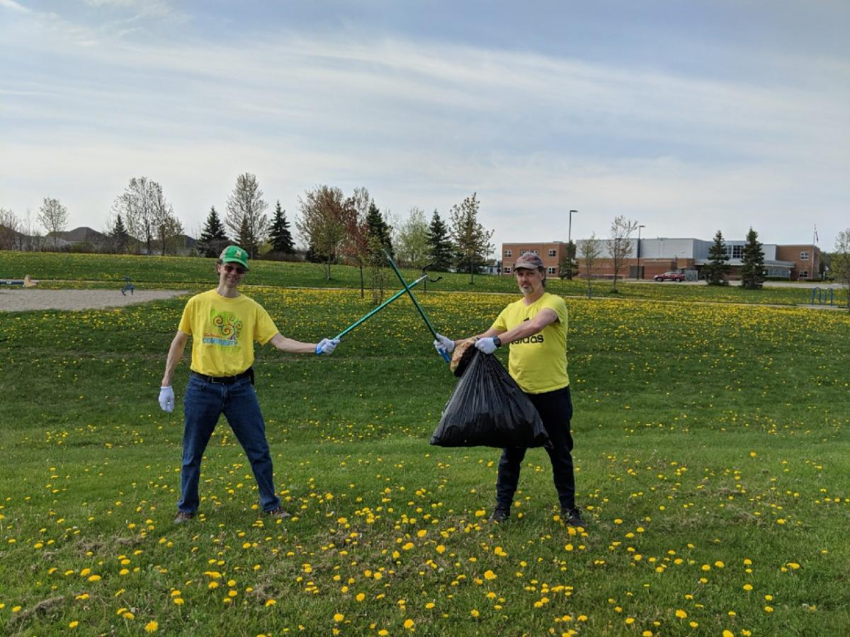 Two people holding garbage bags outside