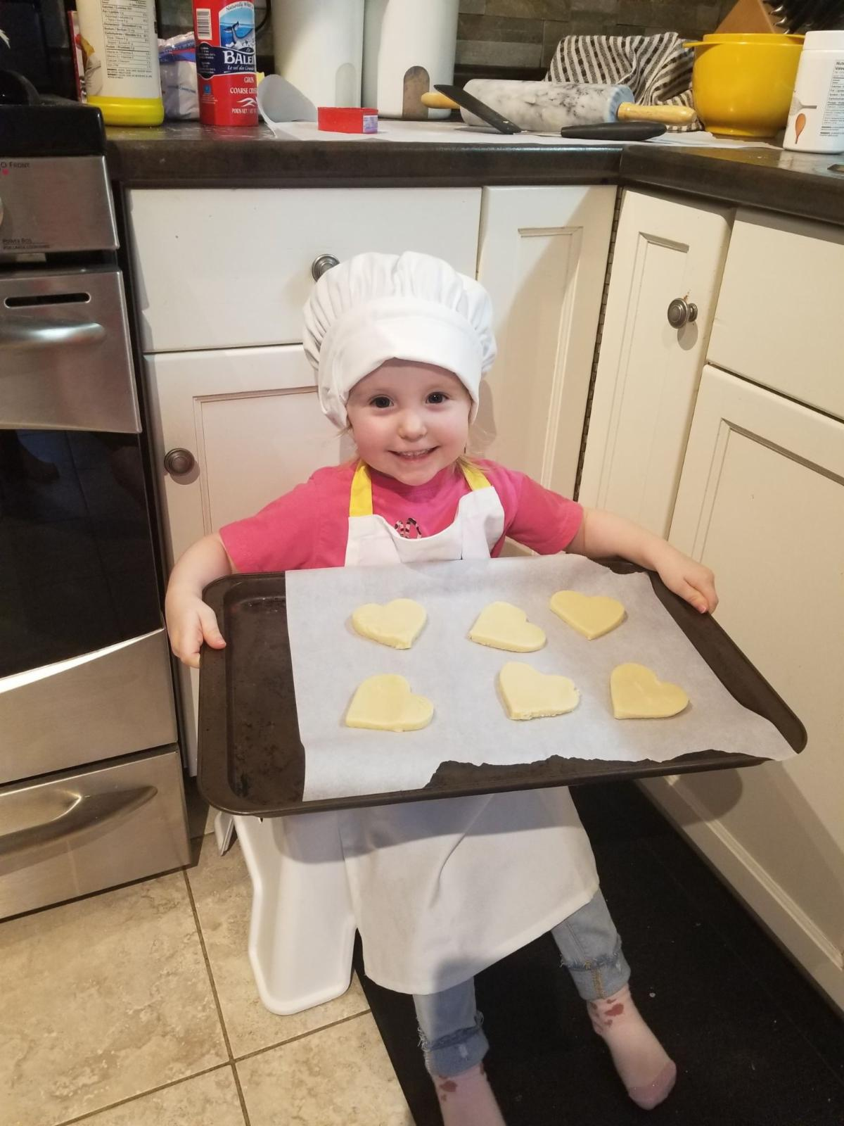 Small child wearing a white and apron proudly holding a tray of heart-shaped cookies.