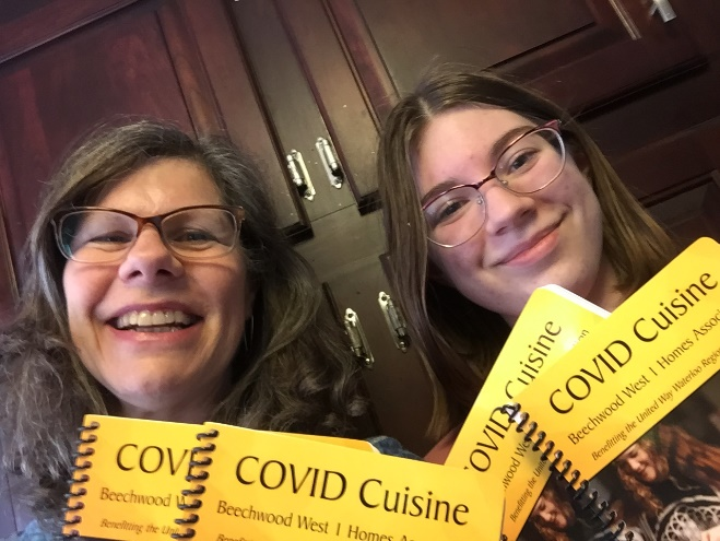 Two smiling people holding copies of the cookbook.