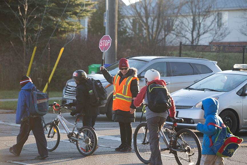 A crossing guard helping students get across the street safely
