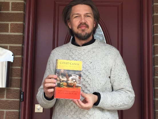 A person standing on their porch with a copy of the cookbook.