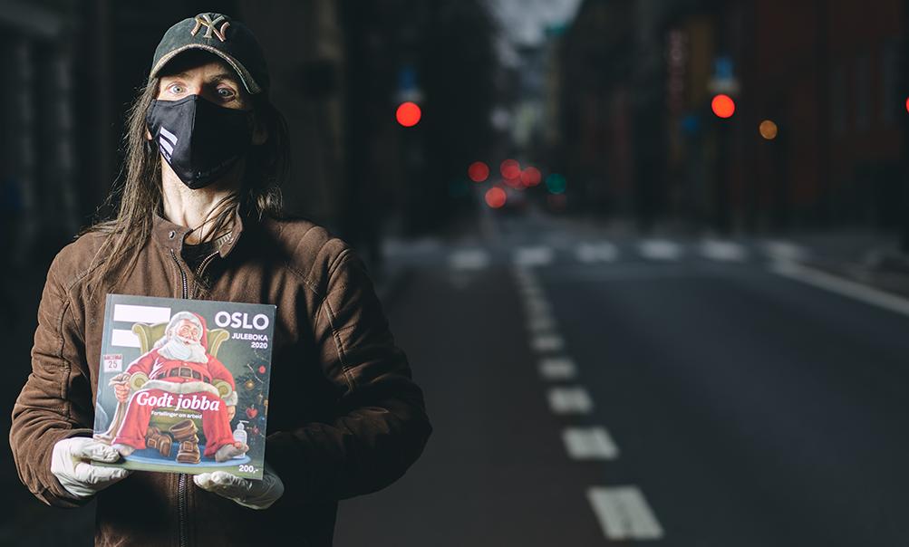=Oslo-selger holder Juleboka 2020 med hansker og munnbind på.