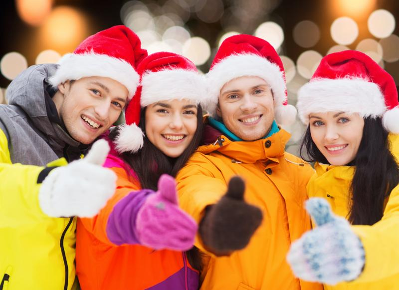 winter holidays, friendship and people concept - happy friends in santa hats and ski suits outdoors showing thumbs up gesture over christmas lights background