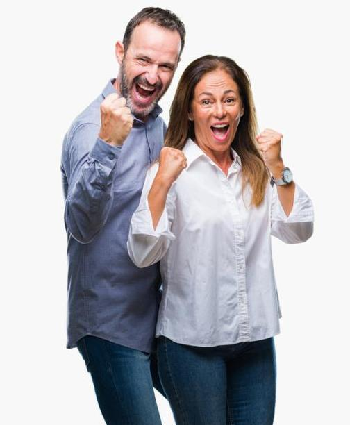 Middle age hispanic business couple over isolated background celebrating surprised and amazed for success with arms raised and open eyes. Winner concept.