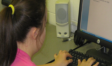 Young woman typing at a computer