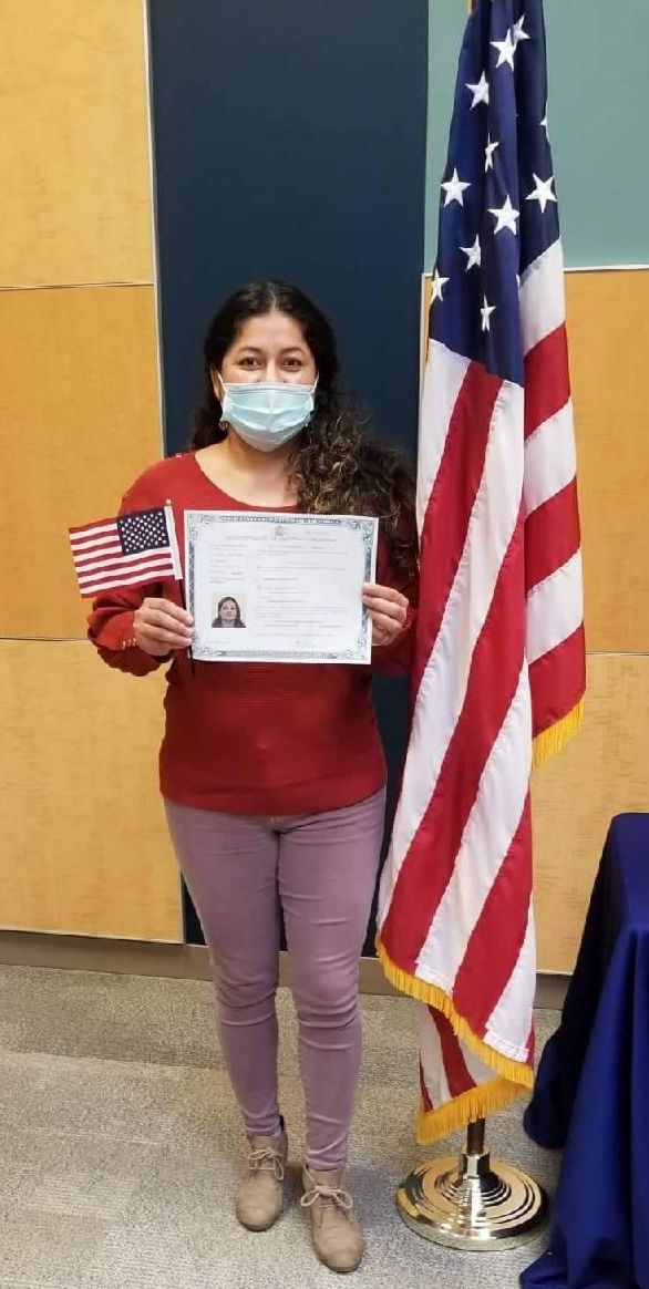 Yosiris, wearing a mask, standing next to American flag, holding small flag and certificate