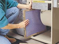 person changing a furnace air filter