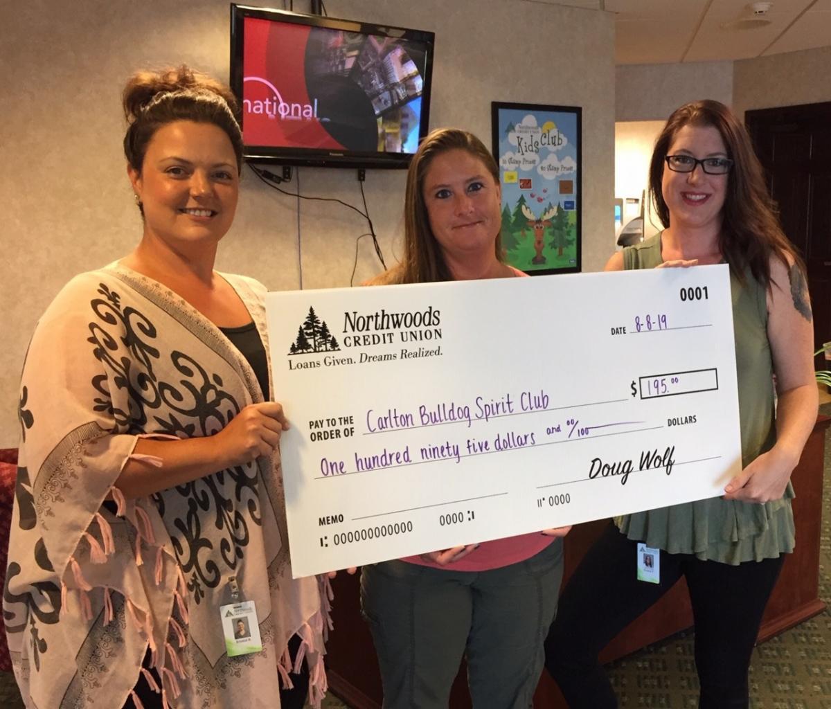 Northwoods CU employees presenting large check to Teresa of the Carlton Bulldog Spirit Club