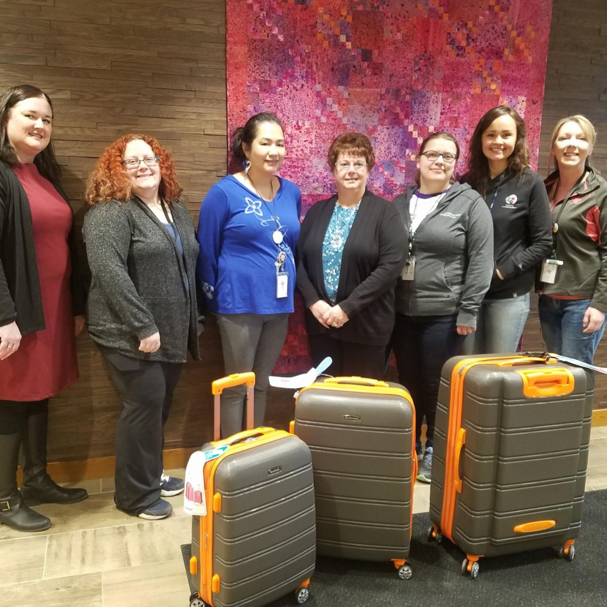 PHoto of NCU staff standing with FDL foster care workers with 3 pieces of luggage, donated by NCU