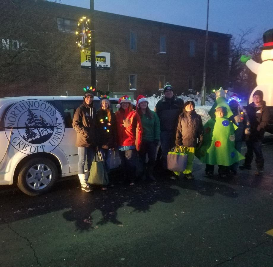 Photo of NCU employees and family in front of the NCU van ready for the Cloquet Home for the Holidays parade to start.