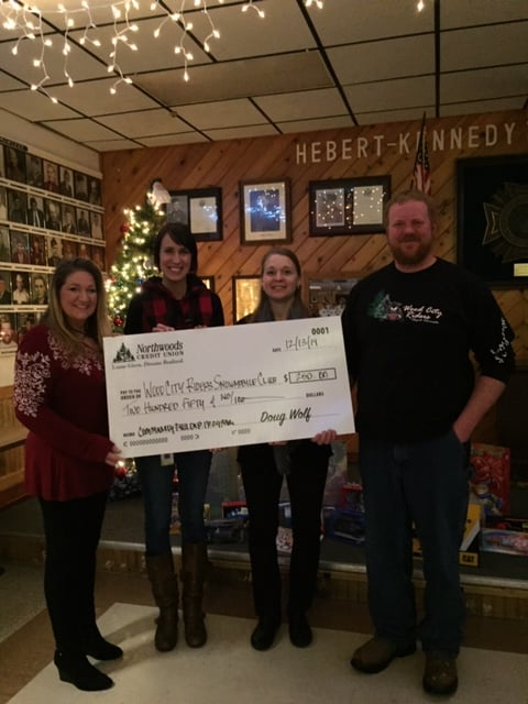 Two Northwoods CU employees presenting large check to two Wood City Riders Club Members.