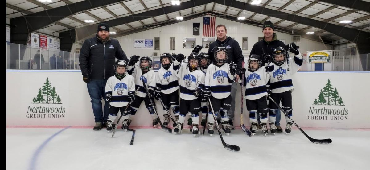 Photo of Mites Hockey Team and coaches at the Carlton Four Seasons Complex in front of the dasher boards with Northwoods Credit Union logos.