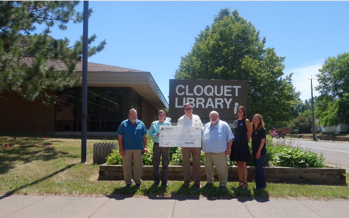 Cloquet Library Board members and NCU Board Members and employees holding large check in front of Cloquet LIbrary sign on 14th Street