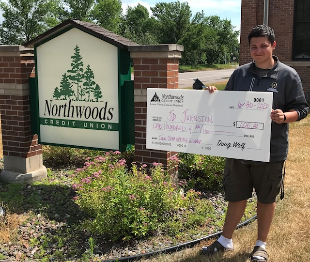 Youth Essay winner JD standing in front of NCU sign with check for $100