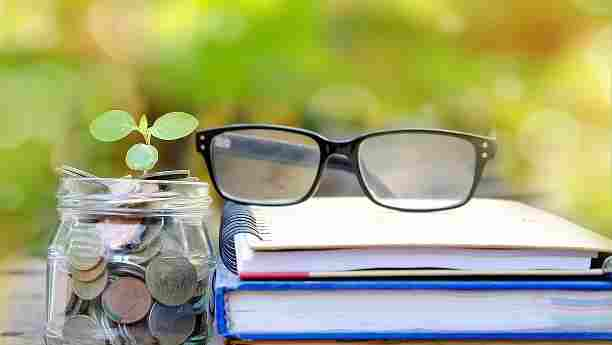 coin jar with small sapling growing out of it next to a pair of eyeglasses on a stack of school books