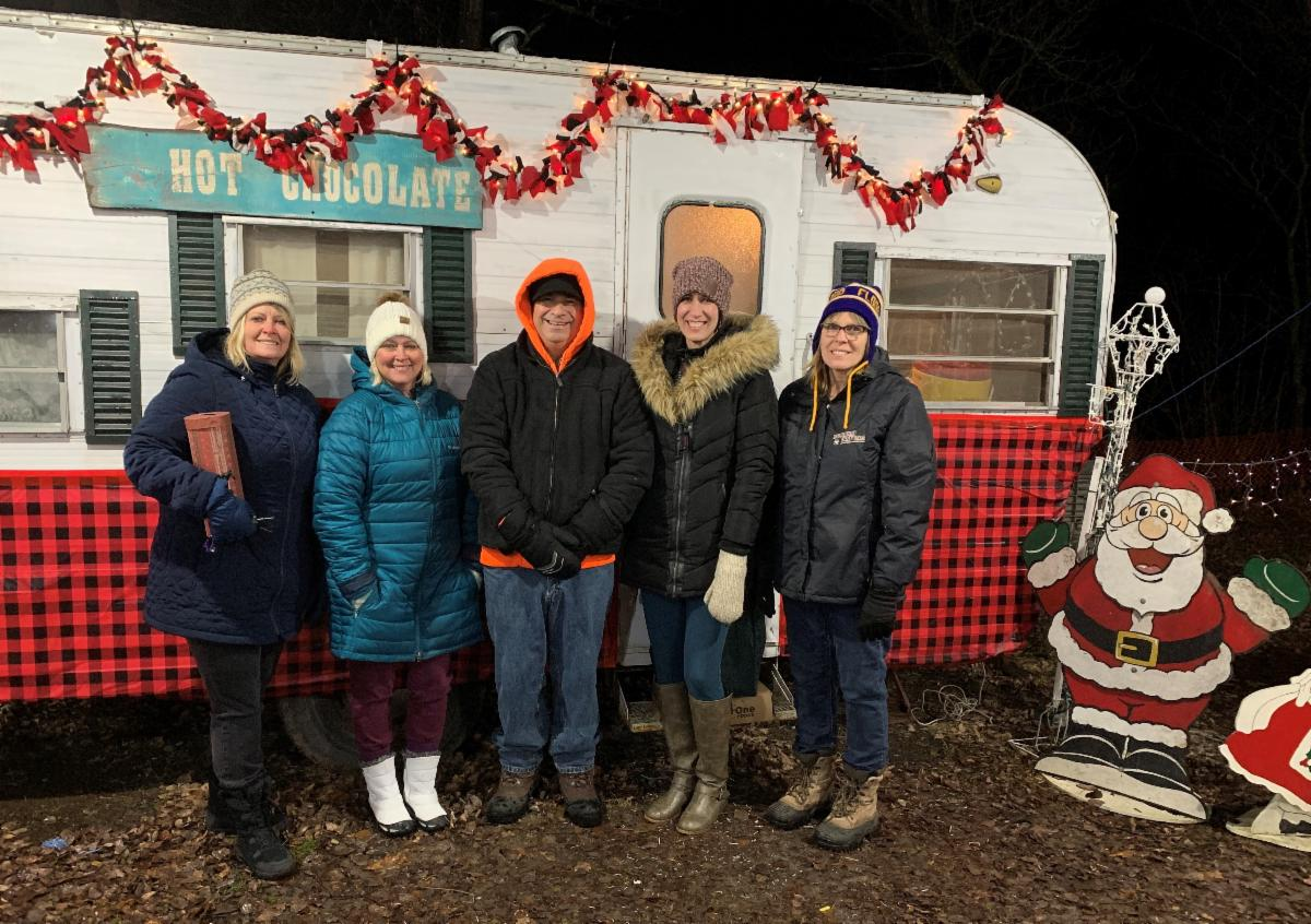Five Northwoods CU employees standing in front of a camper at Floodwood's Christmas in the Campground event.