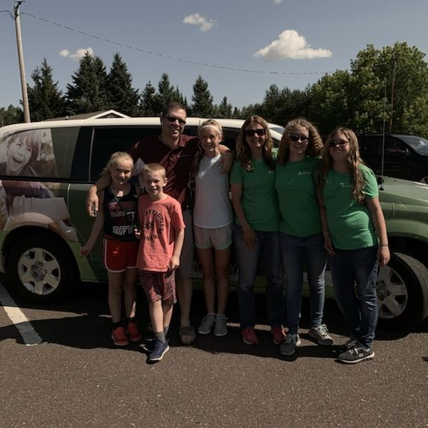 Northwoods CU employees and families standing in front of the NCU Van