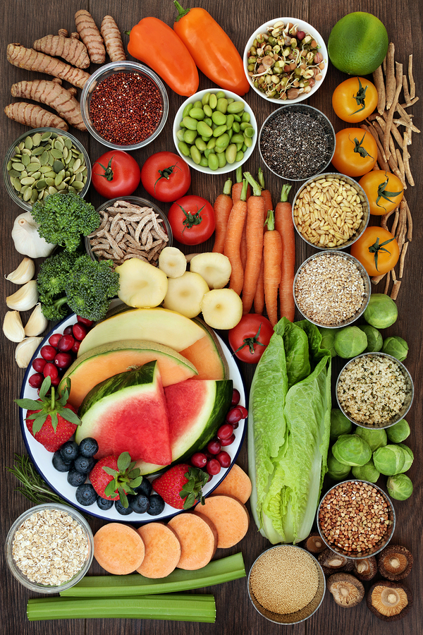 Healthy diet food concept with a selection of fruit, vegetables, seeds, grains, cereals, herbs and spices with foods high in vitamins, minerals, anthocyanins, antioxidants and fibre on oak top view.