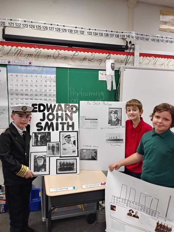 three students pose with Titanic Project Board