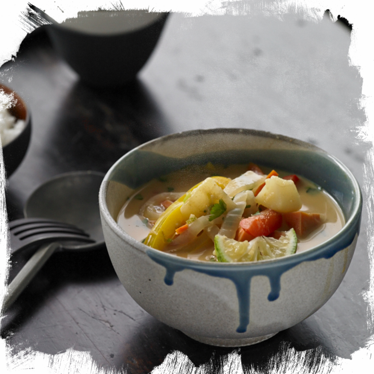 a bowl of thai curry with lime, pears and potatoes in a white bowl with blue accents