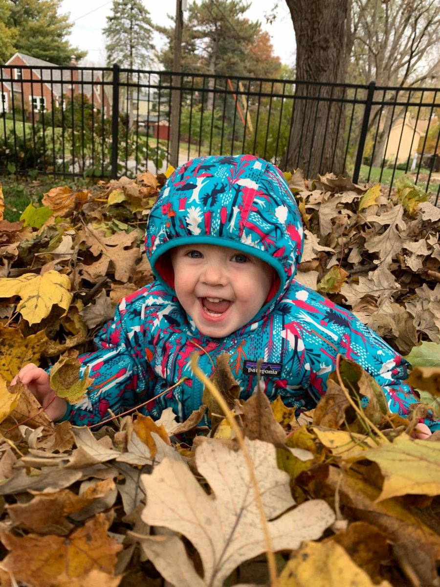 Smiling toddler in a pile of leaves