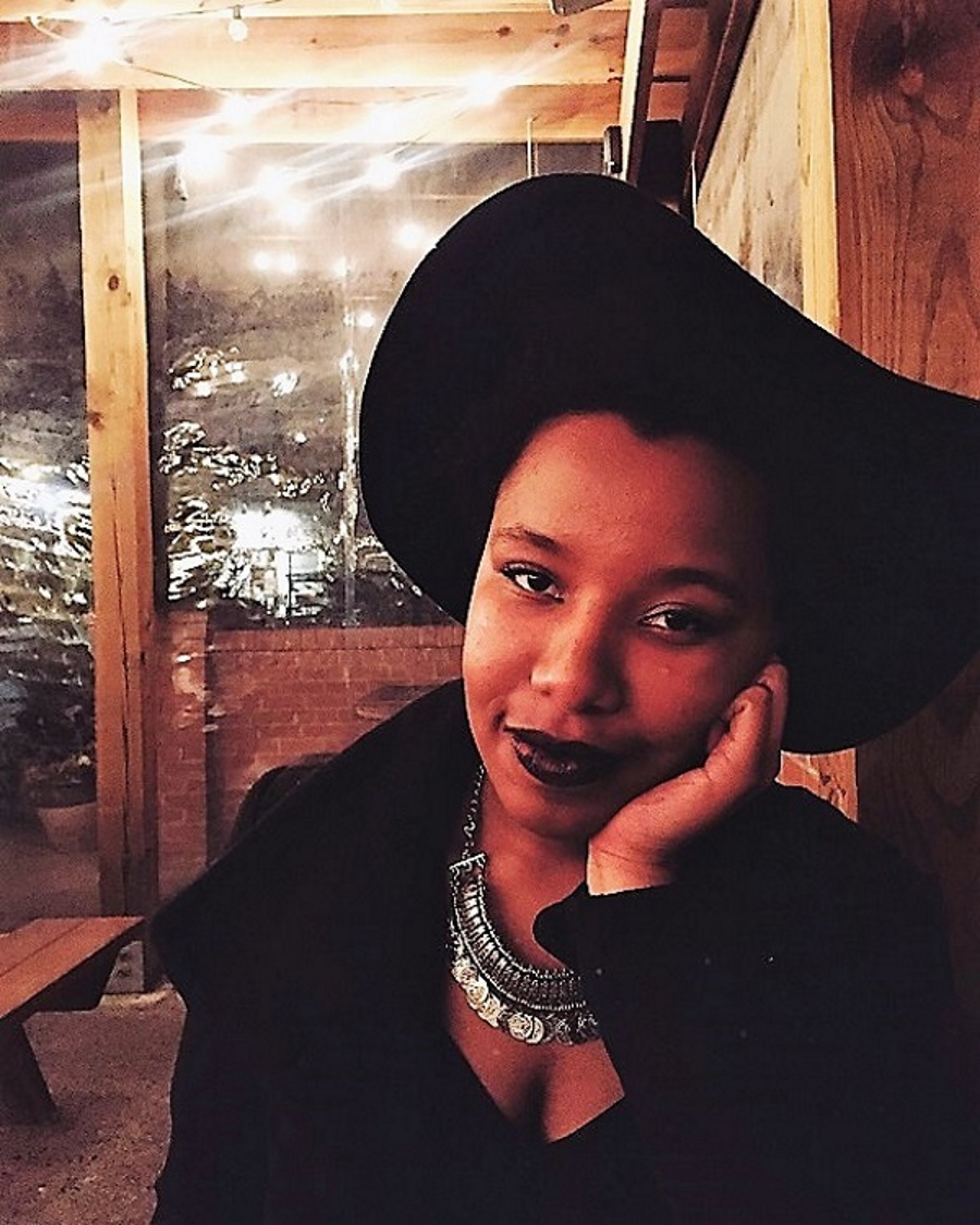 Destiny Hemphill is seated with a brick wall and windows in the background. She looks directly at the camera and smiles as her face rests in the palm of her left hand. Her clothes are black as are her hat and lip color. She wears a silver necklace.