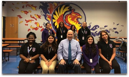Mr. Loftus posing with a group of students in the Orientation Room at Acceleration East High School