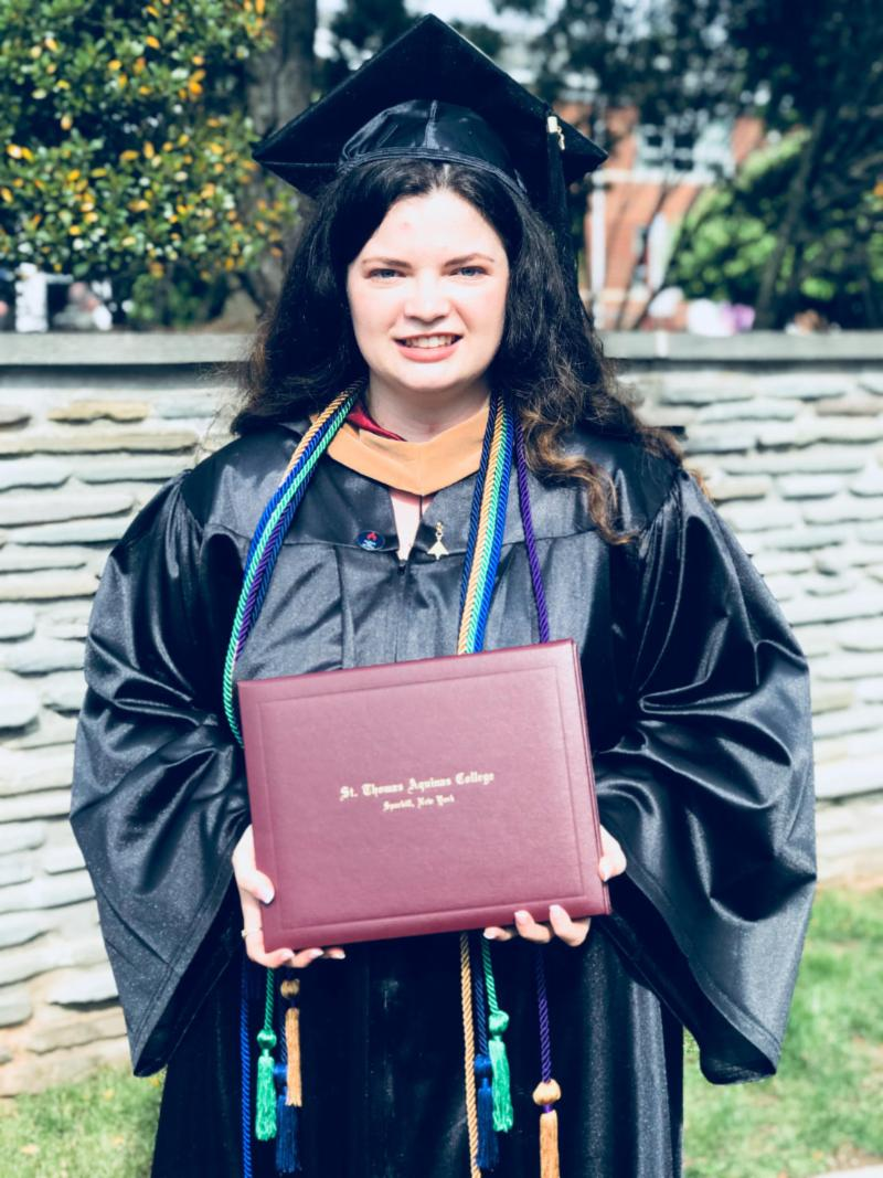 Justine Gizzi, Class of 2019, posing outside with her diploma