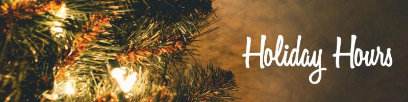 The words holiday hours are written in white over the gold glow of lights from a Christmas tree.
