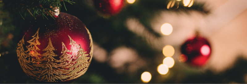 Close up of a red and gold ornament with gold filigree trees on a green christmas tree. There is a blurred background with more red ornaments and strands of lights.