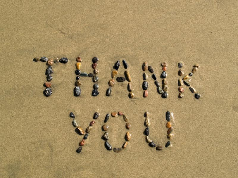 Thank you phrase written on beach sand